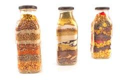 Dekorative Glasflaschen mit den verschiedenen Samen lokalisiert auf Weiß Lizenzfreie Stockbilder