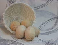Dekorative hölzerne Ostereier in einem Weidenplattenkorb, Holzprodukte lizenzfreies stockbild