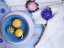 Dekorative Herbstzusammensetzung von Kürbisen, Blumen, Kerzen auf einem hellen hölzernen Hintergrund, Draufsicht Feiertag, Hallow stockfotografie