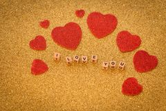 Dekorative Herzen und Beschriftung ich liebe dich auf dem glänzenden goldenen Hintergrund als Symbol der Liebe zusammen mit einem Stockbilder