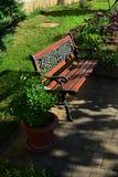 Dekorative Holzbank mit smithcraft auf der Rückenlehne, gesetzt auf Fliesenboden nahe kultivierte Rasen- und Blumentöpfe Lizenzfreies Stockfoto