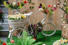 Dekorative Körbe mit Blumen auf einem weißen Fahrrad Stockfotografie