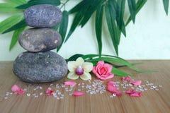 Dekorative Kiesel gestapelt auf eine Zenlebenmode auf einem hölzernen Bambusbrett mit einer rosa Blume und einer Orchidee auf ein Stockfotos