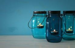 dekorative magische Weckgläser der Weinlese mit Kerze beleuchten auf Holztisch Stockbilder