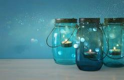 dekorative magische Weckgläser der Weinlese mit Kerze beleuchten auf Holztisch Funkelnüberlagerung Lizenzfreie Stockfotografie