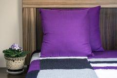 Dekorative purpurrote Kissen und eine Knitdecke auf einem Bett Lizenzfreie Stockfotografie