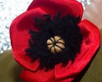 Dekorative rote liegende Mohnblume - auf dem rauen Gewebe vom kakifarbigen Lizenzfreie Stockbilder