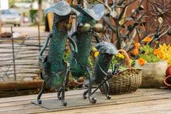 Dekorative Skulptur ` Familie von Gurken ` gemacht vom Metall auf einem Holztisch Lizenzfreies Stockfoto