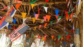 Dekorative Staatsflaggen von den verschiedenen Ländern, die an den Schnüren im hölzernen tropischen Bungalow hängen Exotische ras stock video