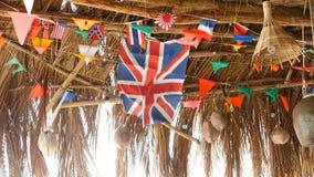 Dekorative Staatsflaggen von den verschiedenen Ländern, die an den Schnüren im hölzernen tropischen Bungalow hängen Exotische ras stock footage