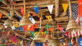 Dekorative Staatsflaggen von den verschiedenen Ländern, die an den Schnüren im hölzernen tropischen Bungalow hängen Exotische ras stock video footage