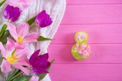 Dekorative Tabelle acht und zarter Blumenstrauß von schönen Tulpen auf rosa hölzernem Hintergrund Stockbild