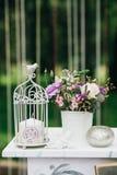 Dekorative weiße Weinlesetabelle für die Hochzeitszeremonie, verziert mit einer Kerze in einem Käfig mit einem Blumenstrauß von B Stockfoto