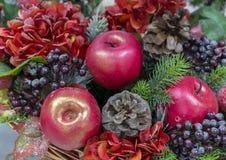 Dekorative Weihnachtszusammensetzung von Äpfeln, von Beeren und von Kiefernkegeln lizenzfreie stockbilder