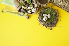 Dekorative Zusammensetzung Ostern auf einem gelben Hintergrund Nest mit Wachteleiern Stockbilder