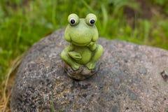 Dekorativer Frosch im Garten keramische Figürchen des grünen Frosches, Frosch, der auf den Steinen sitzt Kopieren Sie Platz Stockfotos
