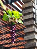 Dekorativer hängender handgefertigter Vase hergestellt von den synthetischen Blumen und von den grünen Pflanzenblättern lizenzfreies stockbild