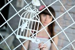 Dekorativer Käfig mit einem Vogel ` s, einem Gitter und auf einem Hintergrund das Mädchen Lizenzfreies Stockfoto