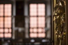 Dekorativer Kopf des goldenen Freskos auf einer Tür in einem edlen Raum stockbild