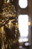 Dekorativer Kopf des goldenen Freskos auf einer Wand in einem edlen Raum stockbild