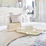 Dekorativer Satz mit Weinlesetasche, Hut, Bücher auf Bett im Luxusschlafzimmer stockfotografie