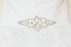 Dekorativer Schmuck mit Bergkristallen und Perlen auf Hochzeitskleid Stockbild