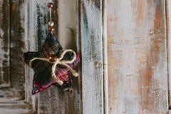 Dekorativer Weihnachtsstern, der am alten Türgriff hängt Lizenzfreie Stockfotografie