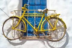 Dekoratives Fahrrad, das von einem Fenster in einem griechischen Haus hängt Stockbilder