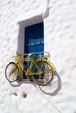Dekoratives Fahrrad, das von einem Fenster in einem griechischen Haus hängt Lizenzfreie Stockfotos