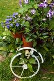 Dekoratives Fahrrad mit Blumen im Garten Stockbild