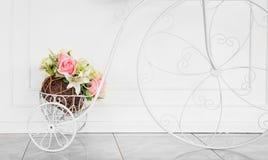 Dekoratives Fahrrad mit künstlichen Blumen auf weißem Wand backgr Stockfotos