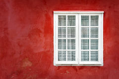Dekoratives Fenster auf einer alten roten Stuckwand lizenzfreie stockfotos