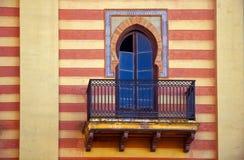 Dekoratives Fenster in der spanischen Art auf der gestreiften Wand lizenzfreie stockfotos