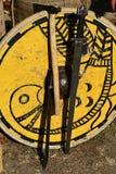 Dekoratives gelbes mittelalterliches rundes Schild mit Vogelmalerei, man übergab Klinge, helle Kampfaxt und machette Lizenzfreie Stockfotografie