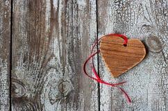 Dekoratives hölzernes Herz mit rotem Band auf einem Holztisch Stockfoto