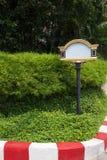 Dekoratives leeres Zeichen auf einem grünen Rasen in einer Fahrstraße, Platz für Text Stockbilder