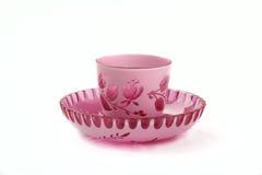 Dekoratives rosa und Weiß färbten klare dekorative KristallTasse und Untertasse lokalisiert auf weißem Hintergrund Stockfotos