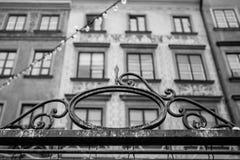 Dekoratives Teil von altem, rostig, Metalltor auf dem Hintergrund der Gruppe alter Fenster Stockfotografie
