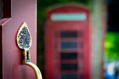 Dekorativt dörrhandtag med det engelska telefonbåset i bakgrunden Arkivbild