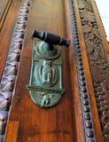 Dekorativt dörrhandtag på rikt dekorerad dörr royaltyfri fotografi