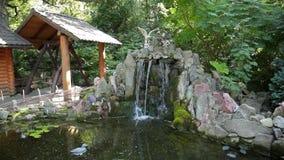 Dekorativt damm med springbrunnen och den guld- fisken i trädgård arkivfilmer