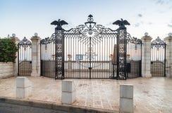Dekorativt dekorerad port med lyktor och dekorativa örnar - övreingången till den Bahai trädgården på gatan Yefe Nof in Fotografering för Bildbyråer