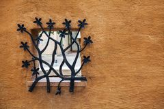 Dekorativt falskt metallgaller på fönstret i stenstaket Royaltyfri Foto