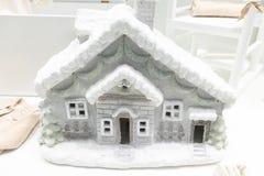 Dekorativt hus för grå plast- vinter med det snöig taket i lagerframdelen royaltyfria bilder
