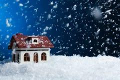 Dekorativt hus i snödriva på färgbakgrund royaltyfria bilder