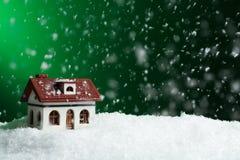 Dekorativt hus i snödriva på färgbakgrund royaltyfria foton