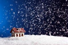 Dekorativt hus i snödriva på färgbakgrund royaltyfri bild