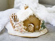 Dekorativt julpepparkakahus i snö arkivfoto