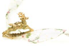 Dekorativt julrenprydnad och band på vit royaltyfri bild