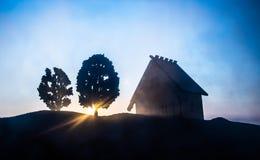 dekorativt litet trähus på solnedgångbakgrunden royaltyfri foto